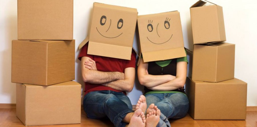 Couple surround by moving boxes sit side by side while wearing smiley faced boxes on their heads