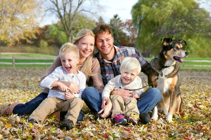 A young family of four and their dog sit in a park surrounded by fall leaves